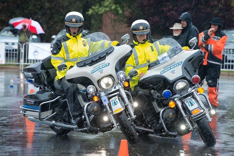 """A team from the Dane County (Texas) Sheriff's Department competes in the Police Motorcycle Street competition in a pouring rain. The team must navigate an obstacle course without parting a 36"""" cord between them. The cord is tied to each motorcycle with two magnets in the center keeping it together. Dulles Expo Center, 4320 Chantilly Shopping Center, Chantilly, Va. 27 June 2015"""