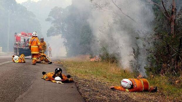 Firefighters resting yesterday during the NSW fires in Australia. There are 65 infernos currently raging in New South Wales.